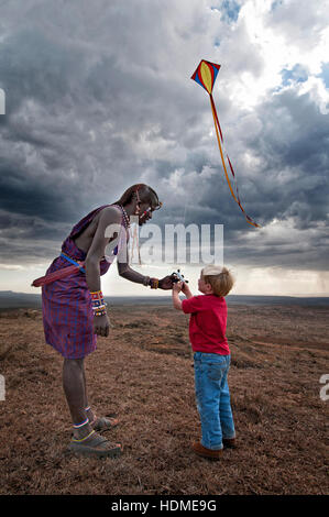 A Maasai Warrior teaches a child to fly a kite with scenic background. Vertical format. Kenya, Africa. - Stock Image
