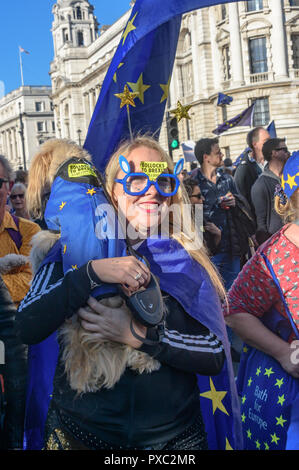 London, UK. 20th October 2018. A woman carries her dog at the end of the People's Vote March calling for a vote to give the final say on the Brexit deal or failure to get a deal. They say the new evidence which has come out since the referendum makes it essential to get a new mandate from the people to leave the EU. With so many on the march the crowding meant many failed to reach Parliament Square and came to a halt in Whitehall. Peter Marshall/Alamy Live News - Stock Image