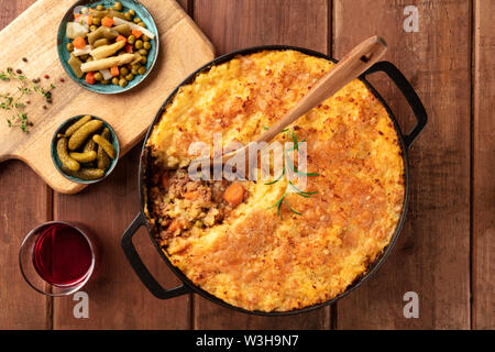 Shepherd's pie in a cooking pan with pickles, herbs, and red wine, overhead shot on a dark rustic wooden background - Stock Image