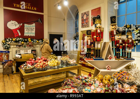 Customers making a purchase at the cash desk in the Fortnum and Mason pop up Christmas shop in Somerset House. Goods on sale include Christmas tree ba - Stock Image