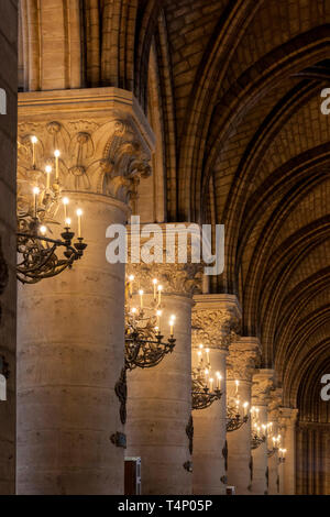 Row of columns and Chandeliers under the arched ceiling of Cathedral Notre Dame, Paris France - Stock Image