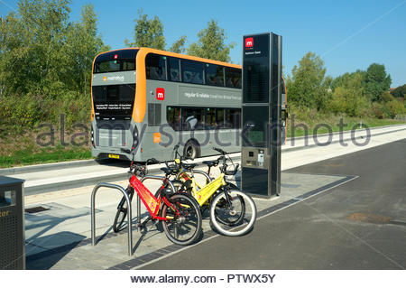 A Bristol Metrobus service departs the Ashton Gate stop, along the guided busway. Hire bicycles are awaiting their next user. Bristol, UK. - Stock Image