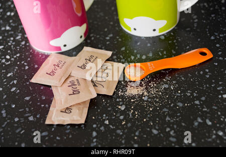 Close up of spoonful of brown sugar and sugar sachets - Stock Image
