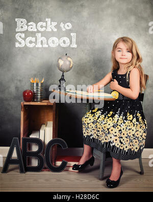 A child student is sitting at a desk with a chalkboard in the background and books for a back to school or education - Stock Image