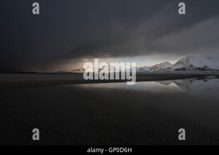 Dark clouds of approaching winter storm cover mountain landscape from Ytresand beach, Moskenesøy, Lofoten Islands, - Stock Image