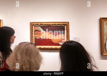 Three women visitors looking the Reclining Nude by Modigliani in The Metropolitan Museum of Art, Manhattan, New York USA - Stock Image