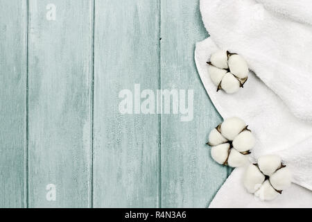 White fluffy towel with cotton boll flowers over a blue green background. Image shot from an overhead top view with free space for text. - Stock Image