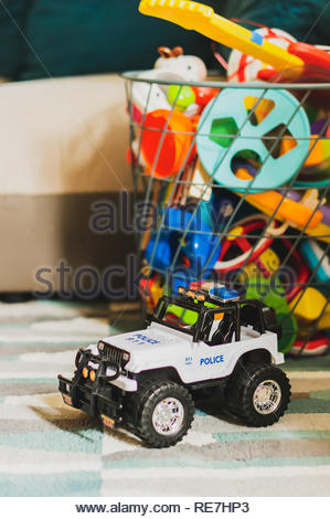 Poznan, Poland - October 27, 2018: Toy police all wheel drive vehicle laying in a carpet next to a grid basket with toys in a room. - Stock Image