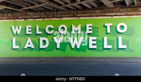 Welcome to Ladywell:  A painted  sign,  under the railway bridge at the junction of Elmira Street and  Ellerdale Street, Lewisham. - Stock Image
