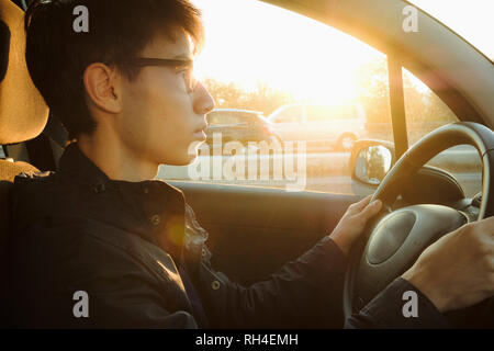 Young man driving car on sunny road - Stock Image