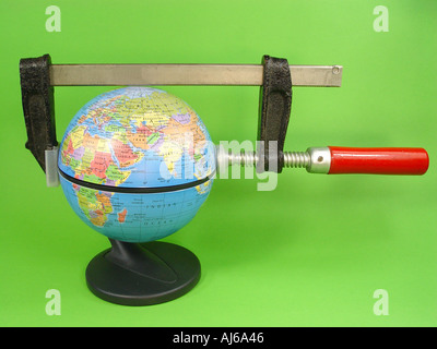 Globe with fastening clamp as symbol for the globe under pressure ecological problems exploitation of the mineral resources e - Stock Image