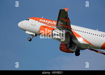 An Easy Jet Airliner climbs out of Inverness Airport on it's return to London Gatwick. - Stock Image