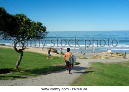A surfer walks towards the sea, in Del Mar (San Diego County) in California, USA. - Stock Image