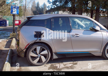 Electric car at charging station showing EV signs in background. - Stock Image