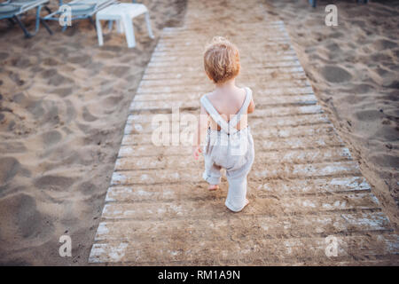 A rear view of small toddler girl walking on beach on summer holiday. - Stock Image