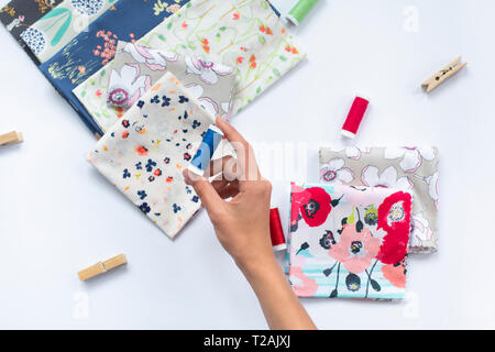 Woman's hand holding blue thread above variety of fabrics - Stock Image