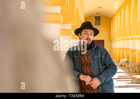 Portrait of a stylish handsome young man with a scarf outdoors.  A serious man wearing a hat and a jaket looking confident at the camera. - Stock Image