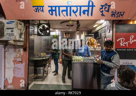 Many young male migrate to different cities in India in search of work. Seen here is a young male from Bihar who is working in a milk shop in Gujarat - Stock Image