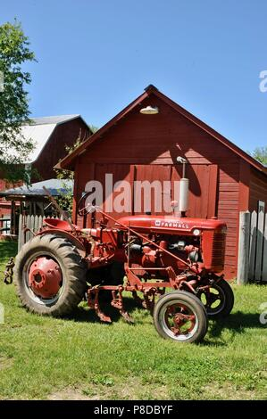 Well maintained, red McCormick Farmall farm tractor parked on farmstead in rural countryside of Wisconsin, USA - Stock Image