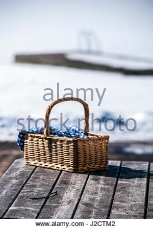 Romantic and cozy to go out in winter for a picnic. with the basket and blue and white chequered cloth. No one is - Stock Image