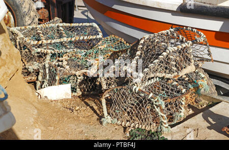 Pots for crabs and lobsters by an inshore fishing boat at West Runton, Norfolk, England, United Kingdom, Europe. - Stock Image
