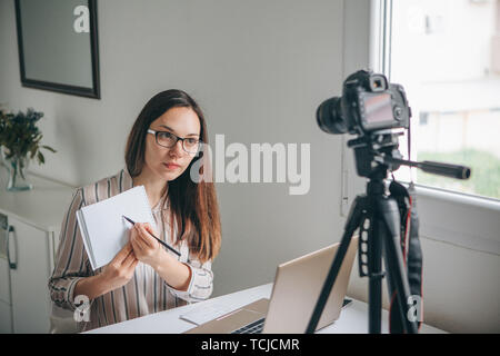 Girl blogger records video for their subscribers. Infobusiness or information business or hobby or online training or education for people. Or language learning - Stock Image