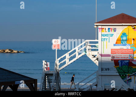 Man walking on the Tayelet beach at sunrise, by a lifeguard booth turned into a temporary luxurious hotel suite part of a promotional tourism project - Stock Image