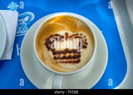 Powdered chocolate in the shape of a crown on a cup of cappuccino coffee, at the Café at the Palace, Holyroodhouse, Edinburgh, Scotland, UK - Stock Image
