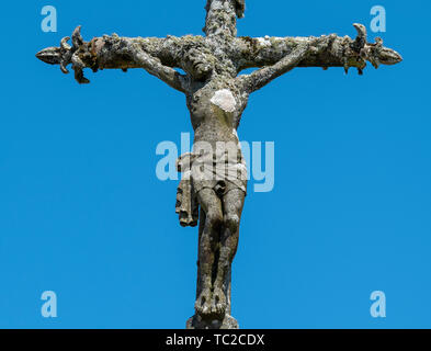 Stone statue of Christ on the cross against a blue sky at a cemetery in La Feuillée, Brittany, France. - Stock Image