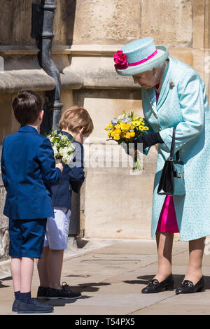Windsor, UK. 21st April 2019. A young boy bows to the Queen after presenting her with a traditional posy of flowers outside St George's Chapel in Windsor Castle following the Easter Sunday service. Credit: Mark Kerrison/Alamy Live News - Stock Image