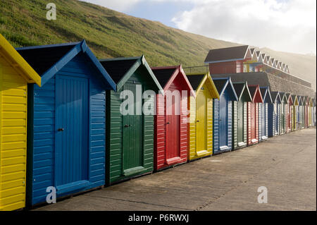 The multicoloured beach huts overlooking Whitby beach on the North Yorkshire coast. - Stock Image