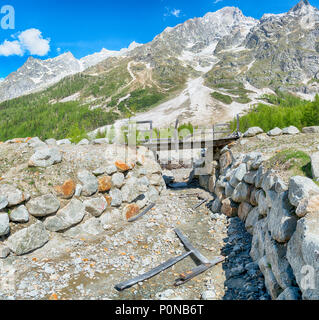 pedestrian bridge destroyed by an avalanche in winter, landscape in Ferret valley with mountains Grandes Jorasses in background - Stock Image