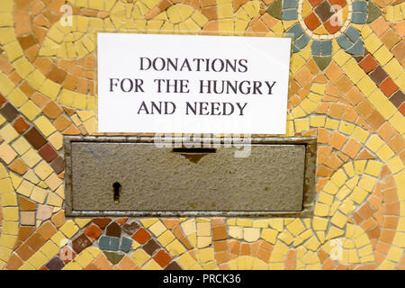 Collection box in a church asking for donations for the hungry and needy. - Stock Image