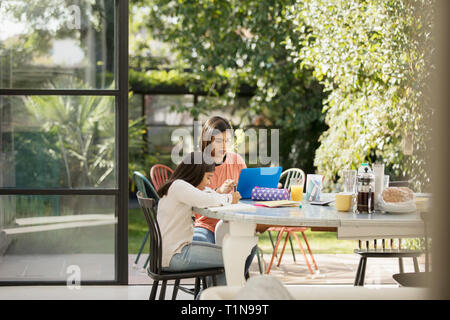 Mother and daughter using laptop and doing homework at table - Stock Image