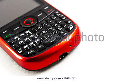 qwerty keypad and navigation key on red old phone isolated white background - Stock Image