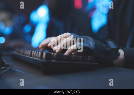Close-up of unrecognizable hacker in black fingerless gloves sitting at desk and typing on computer keyboard while working on virus - Stock Image