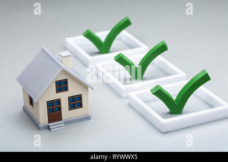 Close-up Of A Tick Sign Near The House Model On Desk - Stock Image