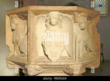 A view of the medieval octagonal font panels in the parish church of St Mary at Shelton, Norfolk, England, United Kingdom, Europe. - Stock Image