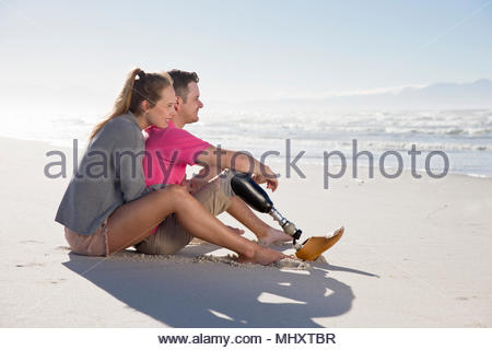 Man With Artificial Leg Sitting And Relaxing With Female Partner On Beach Vacation - Stock Image