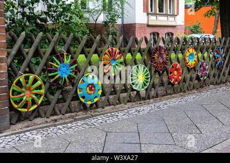 Unusual garden fence . Trellis-style wood logs & painted hubcaps . Karwendel strasse, Berlin-Lichterfelde - Stock Image