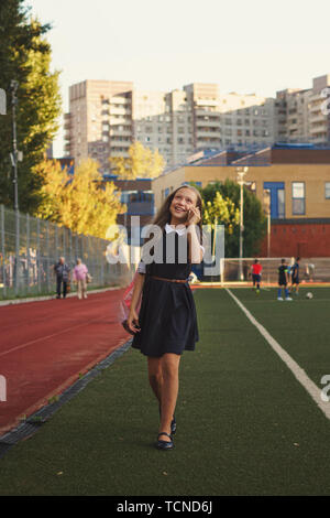 Cute little schoolgirl walks on sports ground and talks on a smartphone. She walks on lawn of a football field in school uniform - dress and shoes. Sh - Stock Image