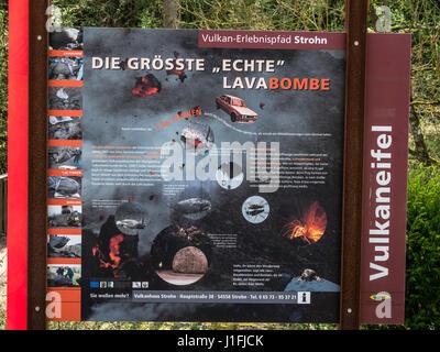 Poster describing volcanic phenomens, largest lava bomb exhibited in village Strohn, near Daun, volcanic region, - Stock Image