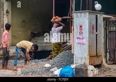 Builders carry bricks on their head whilst building a wall in Chennai, India, where - Stock Image