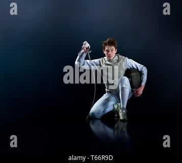 Portrait confident teenage boy fencing - Stock Image