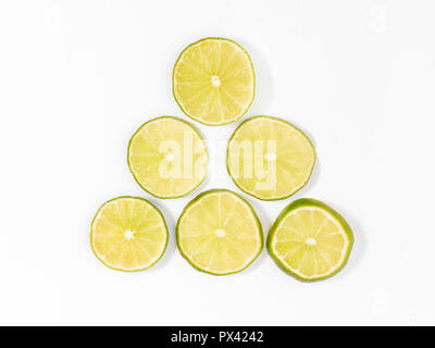 sliced limes on a white background - Stock Image