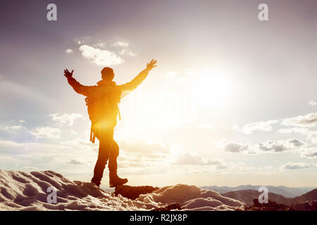 Man stands in winner pose with raised arms on mountain top. Trekking or win concept - Stock Image