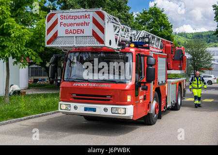 Iveco Magirus 160E30 turntable ladder truck of a Swiss fire brigade. Ladder and platform retracted. Fireman standing - Stock Image