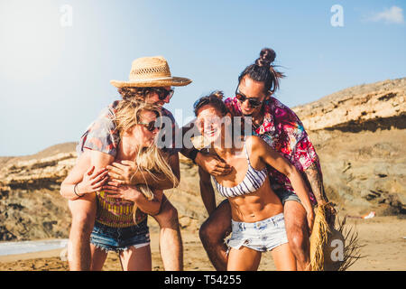 Cheerful people two couples laugh and have fun together - friends enjoying the summer holiday vacation at the berach - girls carrying boys - beautiful - Stock Image