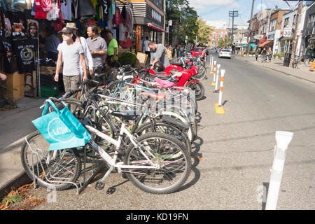 Long row of bicycles outside t-shirt store in Kensington Market in downtown Toronto, Ontario, Canada - Stock Image