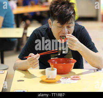 Local man eating a vegetable dish bought from one of the many small food kiosks in the indoor market of the ethnic district of Little India Singapore. - Stock Image